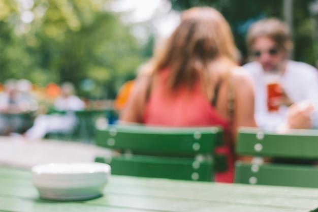 いくつかの女と男がテーブルに座っての背面図と背景をぼかした写真