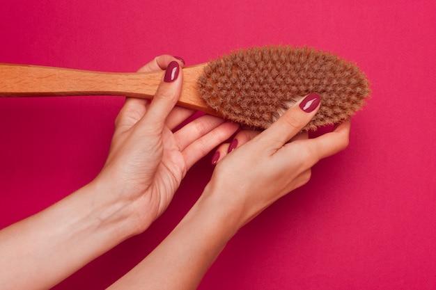 女性の手は、天然の木の柄とイノシシの毛が付いたマッサージブラシを持っています。