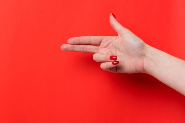 Женская рука показывает жест знак пистолет на красном фоне. место для текста