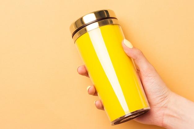 暖かい黄色の背景に飲み物の黄色の空のサーモカップを持っている女性の手