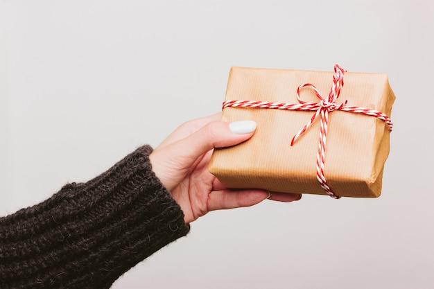 黒いウールのセーターの女の子は、ひだで結ばれた紙に包まれたクリスマスプレゼントを保持します
