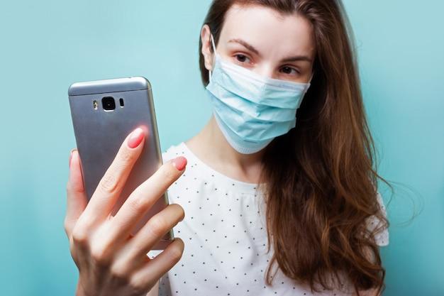 コロナウイルス流行時の分離。使い捨ての医療用マスクと病院の服を着た女の子が病院で自撮りをします。