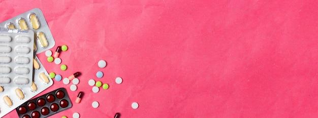 Разноцветные таблетки и гранулы в блистере разбросаны на розовом фоне. медицинская концепция баннер вид сверху. слайд место для текста.