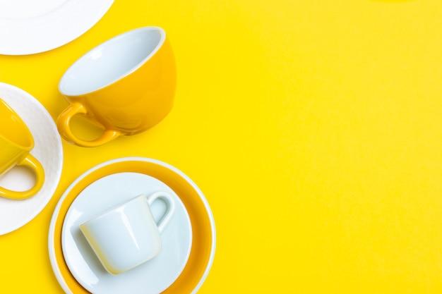 多くの異なるセラミック皿、空のコーヒーのペア、プレート、明るい黄色の背景上のカップ