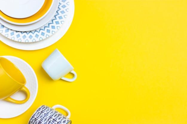 明るい黄色の背景にさまざまなセラミック皿、空のコーヒーのペア、プレート、カップがたくさん。オブジェクトの抽象的な装飾