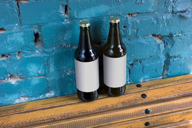 Две бутылки пива с пустыми метками стоят на деревянной подставке на фоне кирпичной стены