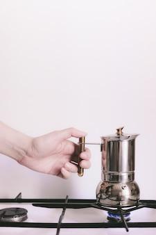女性の手がガスストーブの間欠泉のコーヒーメーカーを保持しています。自宅でコーヒーを作る