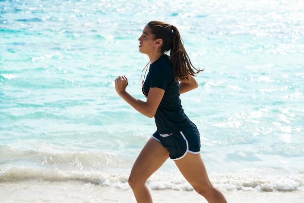 カリブ海の海岸のビーチで走っているラテンの女の子