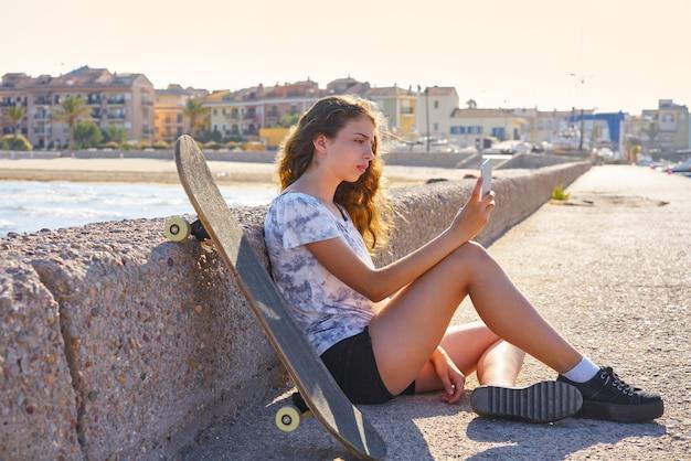 スマートフォンが座っているローラースケート少女