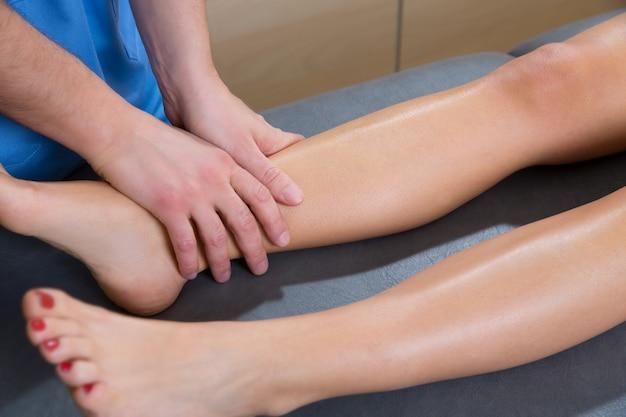 リンパ排水マッサージセラピスト女性の足に手します。