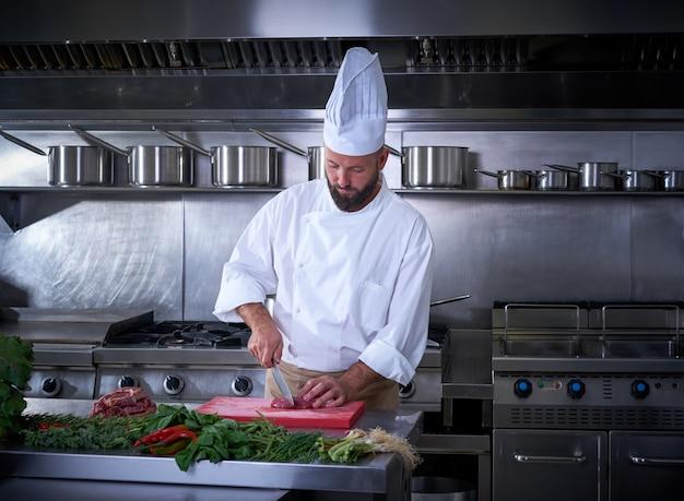 レストランのキッチンで肉を切るシェフ