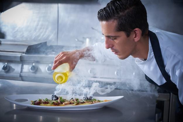 煙が付いている台所でタコを準備するシェフ