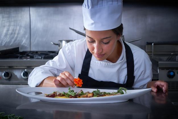 シェフの女性が台所で皿に花を飾る