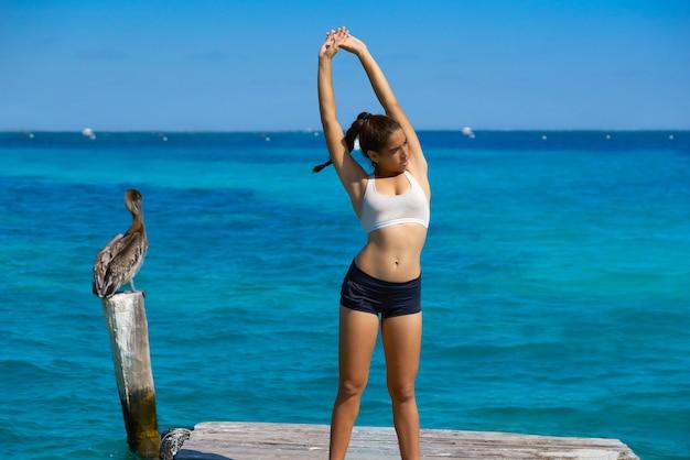 カリブ海でストレッチラテンアスリート女性