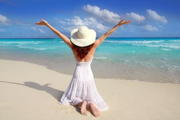 Карибский пляж женщина сзади на коленях с распростертыми объятиями
