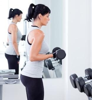 スポーツジムでウエイトトレーニング機器を持つ女性