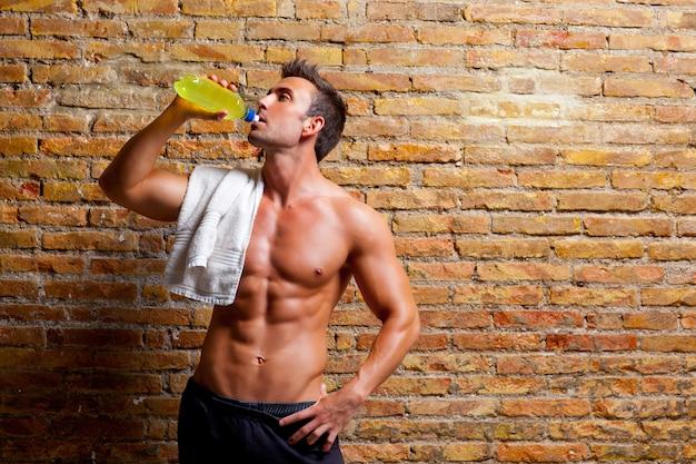 筋肉形のジムで男リラックスした飲酒
