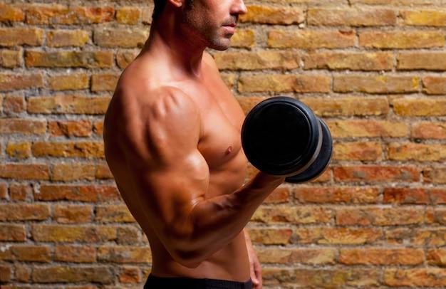 筋肉形のレンガの壁に重みを持つボディ男
