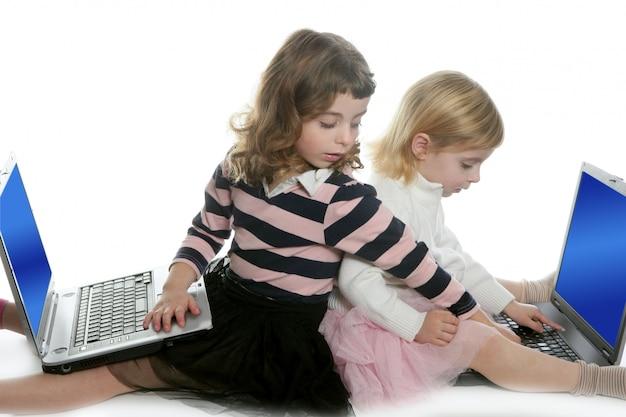コンピューターのラップトップと二人の少女姉妹