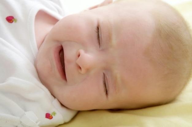 ベッドの上に敷設泣いている悲しい赤ちゃん