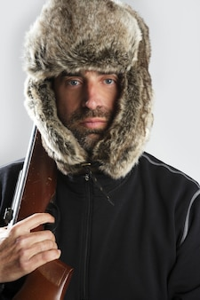 Охотник зима меховая шапка мужской портрет держит пистолет
