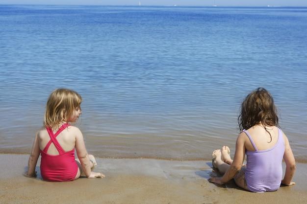 牽引姉妹はビーチ水着水着に座っています