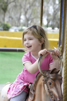 馬を遊んで小さなブロンドの女の子は陽気に行く