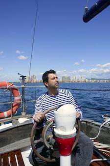 ビンテージ木製ヨット海の上の青い船乗り