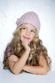 笑顔のジェスチャー小さな女の子冬ピンクキャップの肖像画