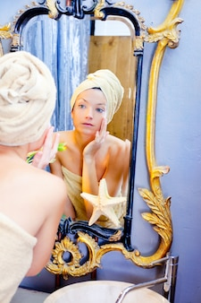 黄金の鏡を見てタオルで美容女性