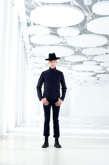 モダンな屋内で帽子を持つ黒の極西現代ファッション男