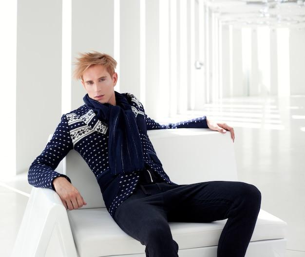 白い屋内に座っている現代の金髪男性未来的なサイエンスフィクション