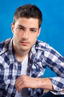 Красивый молодой человек в клетчатой рубашке на синем