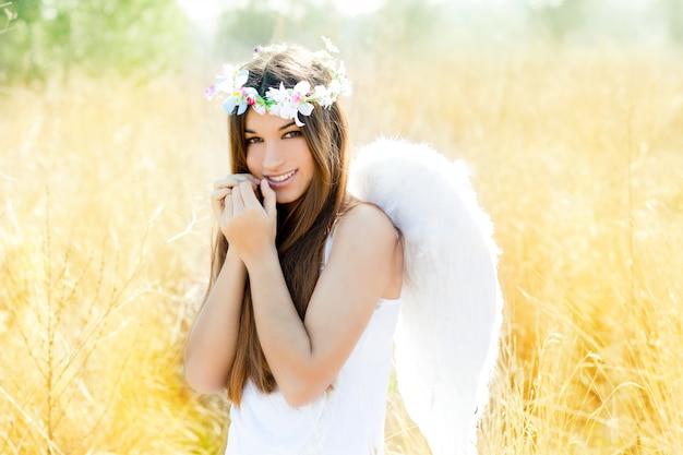 羽の白い翼を持つゴールデンフィールドの天使の女の子