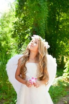 天使の子供女の子空を探して手に花を持つ