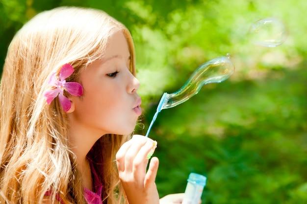 屋外の森でシャボン玉を吹く子供たち