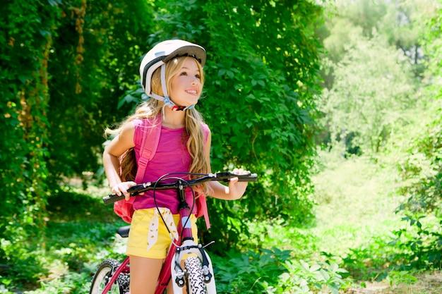 子供の女の子が森の笑顔で屋外自転車に乗って