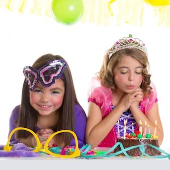 子供の幸せな女の子の誕生日パーティーケーキを吹いて