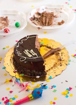 半分チョコレートケーキスライスとパーティーのこどもの端