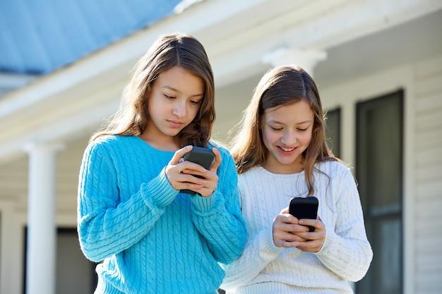 テクノロジースマートフォンを楽しんでいる姉妹双子