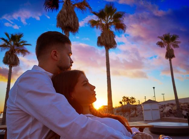 Молодые пары в восходе солнца каникул пляжа