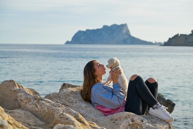 ビーチでマルチチョン犬と遊んでいるガールフレンド