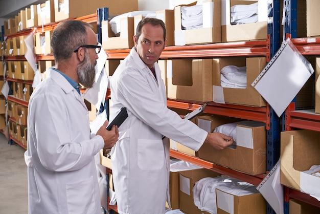 繊維の倉庫のスーパーバイザーおよびマネージャーの人
