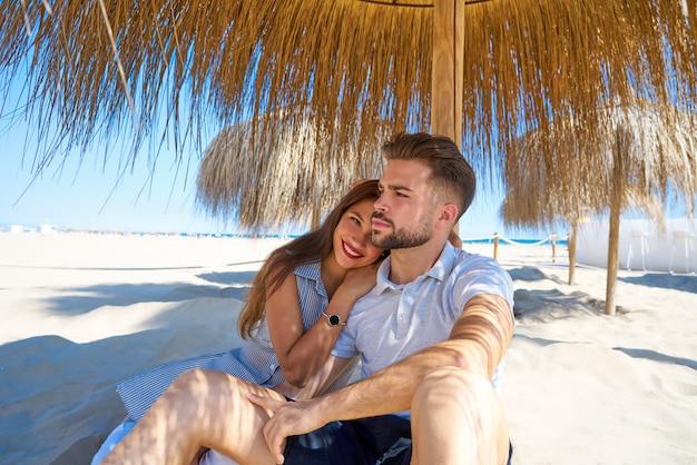 若いカップルは日傘の下でビーチで抱擁します。