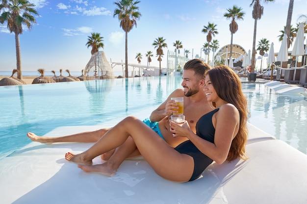 ビーチリゾートでプールハンモックで若いカップル