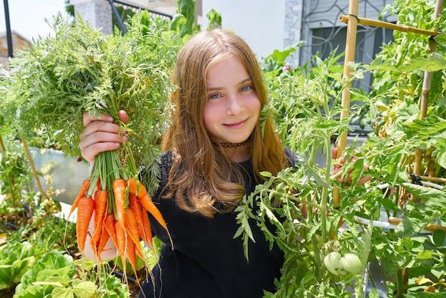 ブロンドの女の子がニンジン都市果樹園を収穫