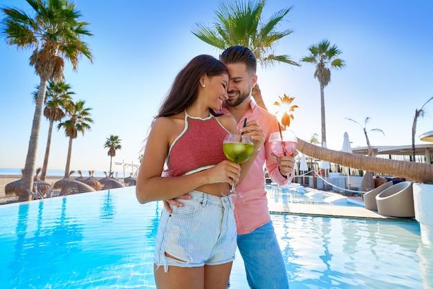 若いカップルのプールリゾートでカクテルを飲む