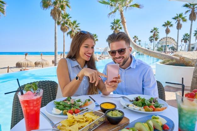 Молодая пара с смартфон в ресторане у бассейна