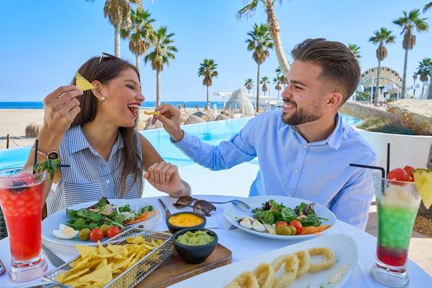Молодая пара ест в ресторане у бассейна