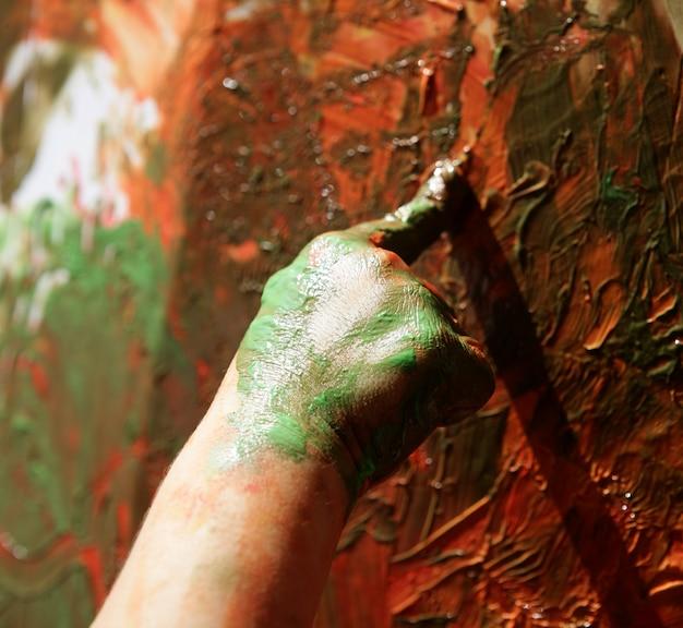子供アーティストの手が多色を塗る